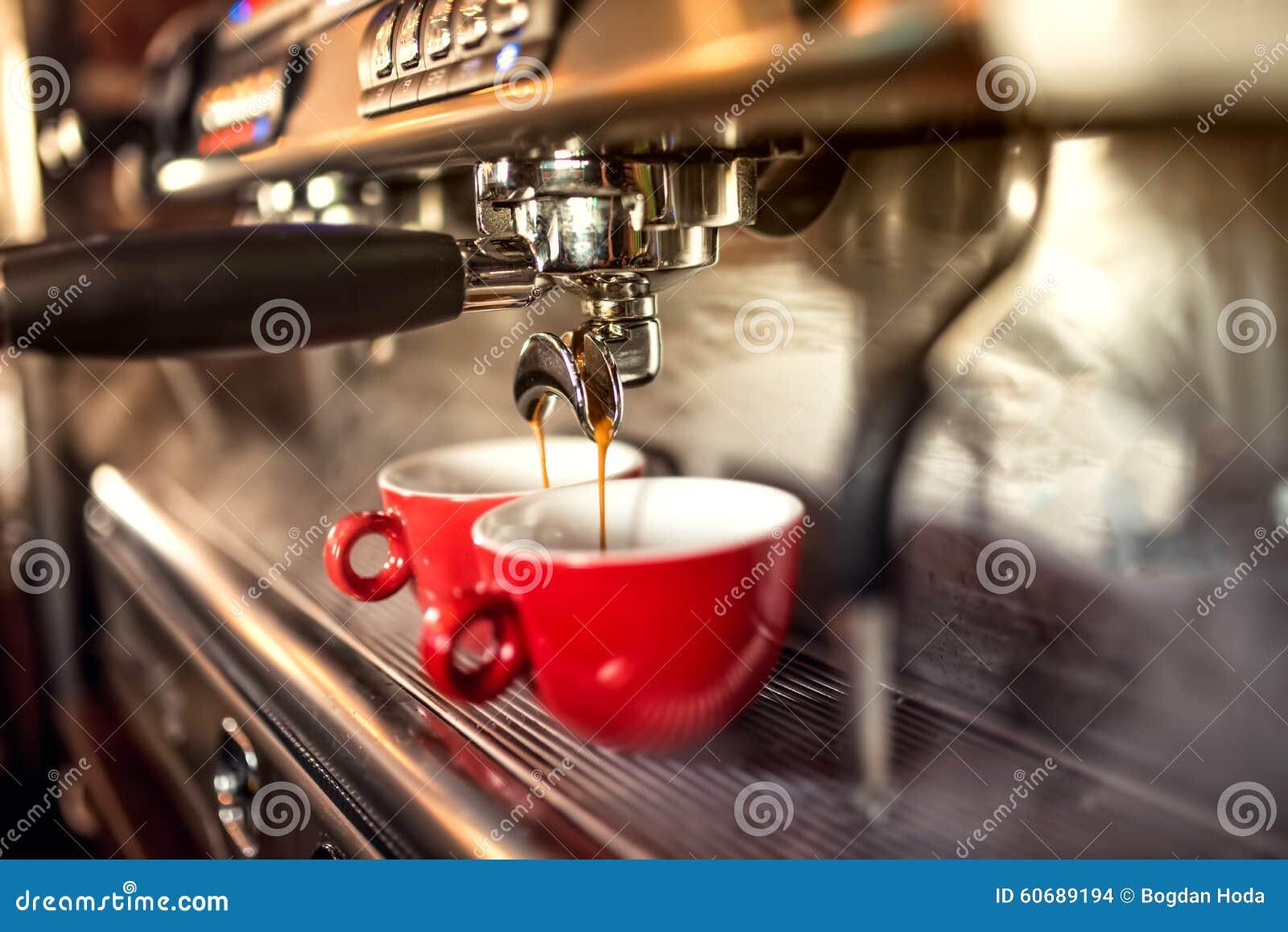 Máquina do café que prepara o café fresco e que derrama em copos vermelhos no restaurante, na barra ou no bar