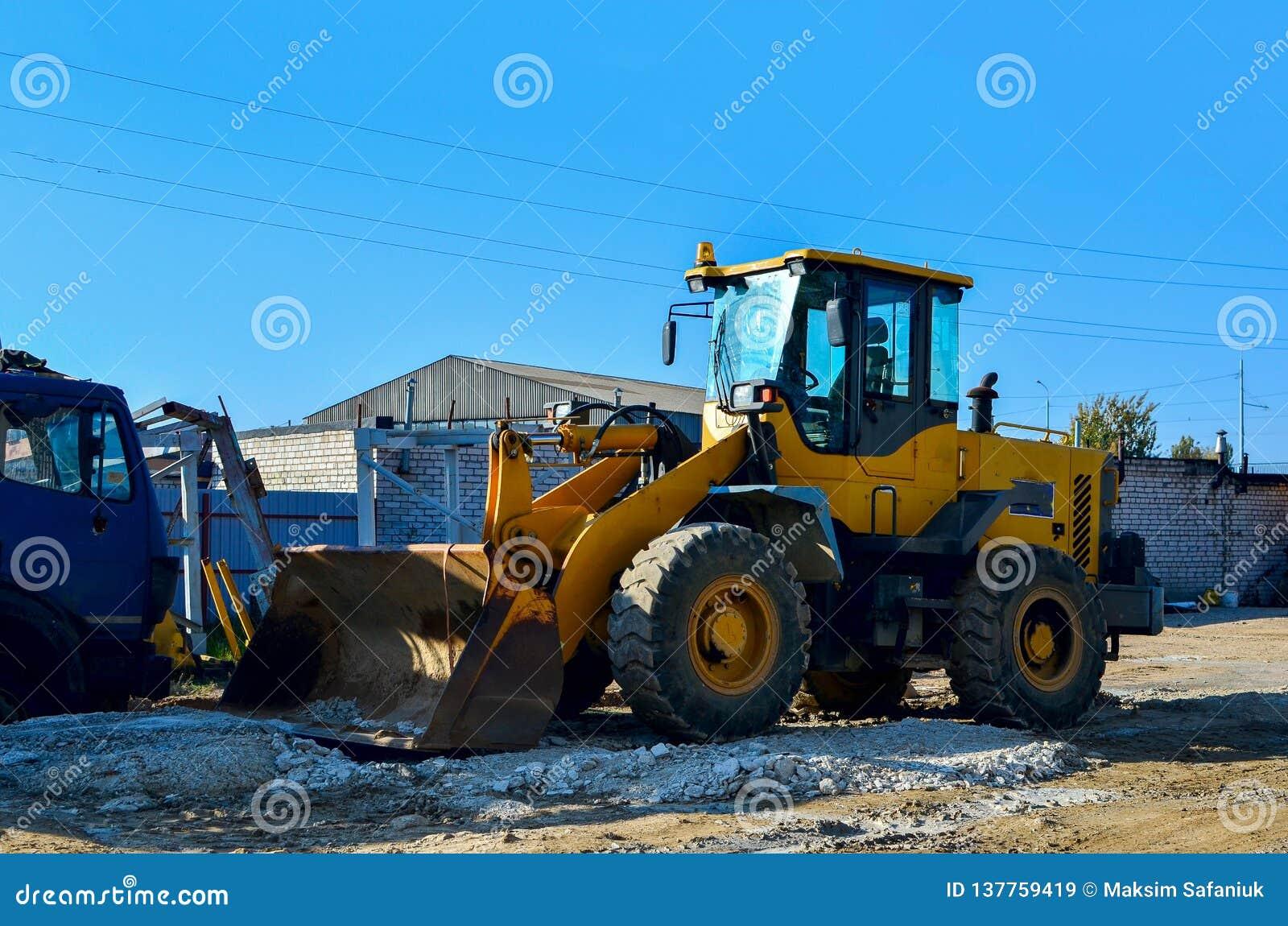 A máquina escavadora no canteiro de obras está preparando-se para carregar o solo no caminhão basculante Carregador da roda com c
