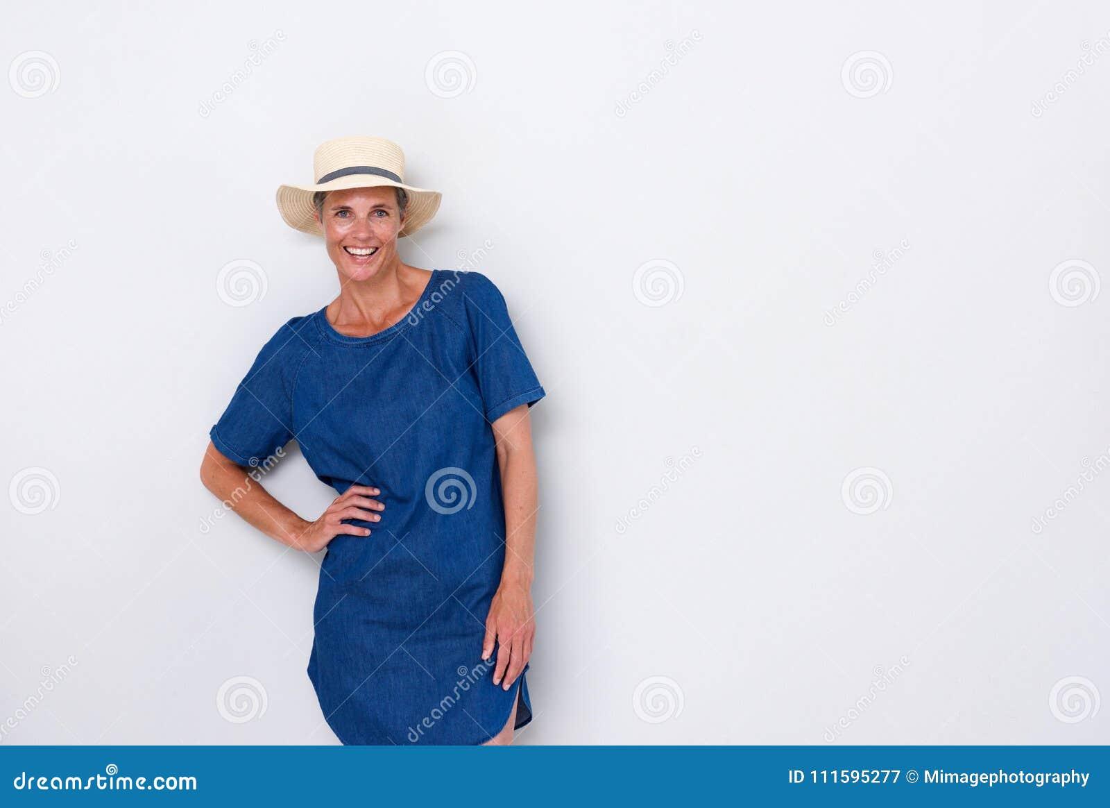 Más vieja mujer hermosa que sonríe con el sombrero contra el fondo blanco