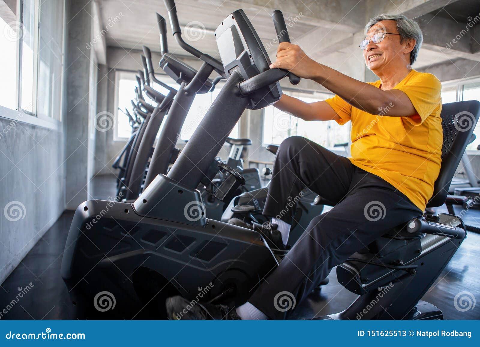 Más viejo hombre mayor que ejercita en la máquina de ciclo que se relaja en gimnasio de la aptitud envejecido Viejo entrenamiento