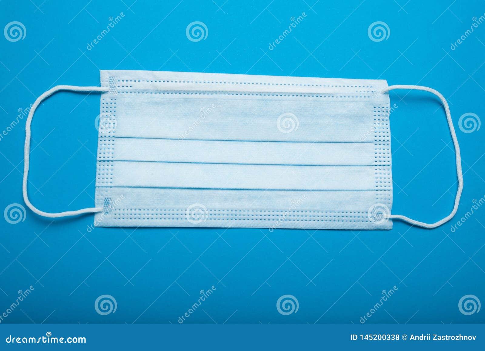 Máscara cirúrgica do Orelha-laço no fundo azul, conceito