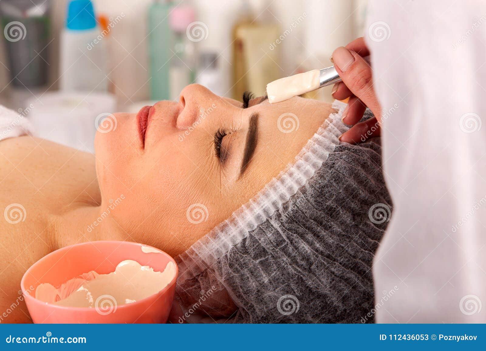 Máscara protetora do colagênio Tratamento facial da pele Mulher que recebe o procedimento cosmético