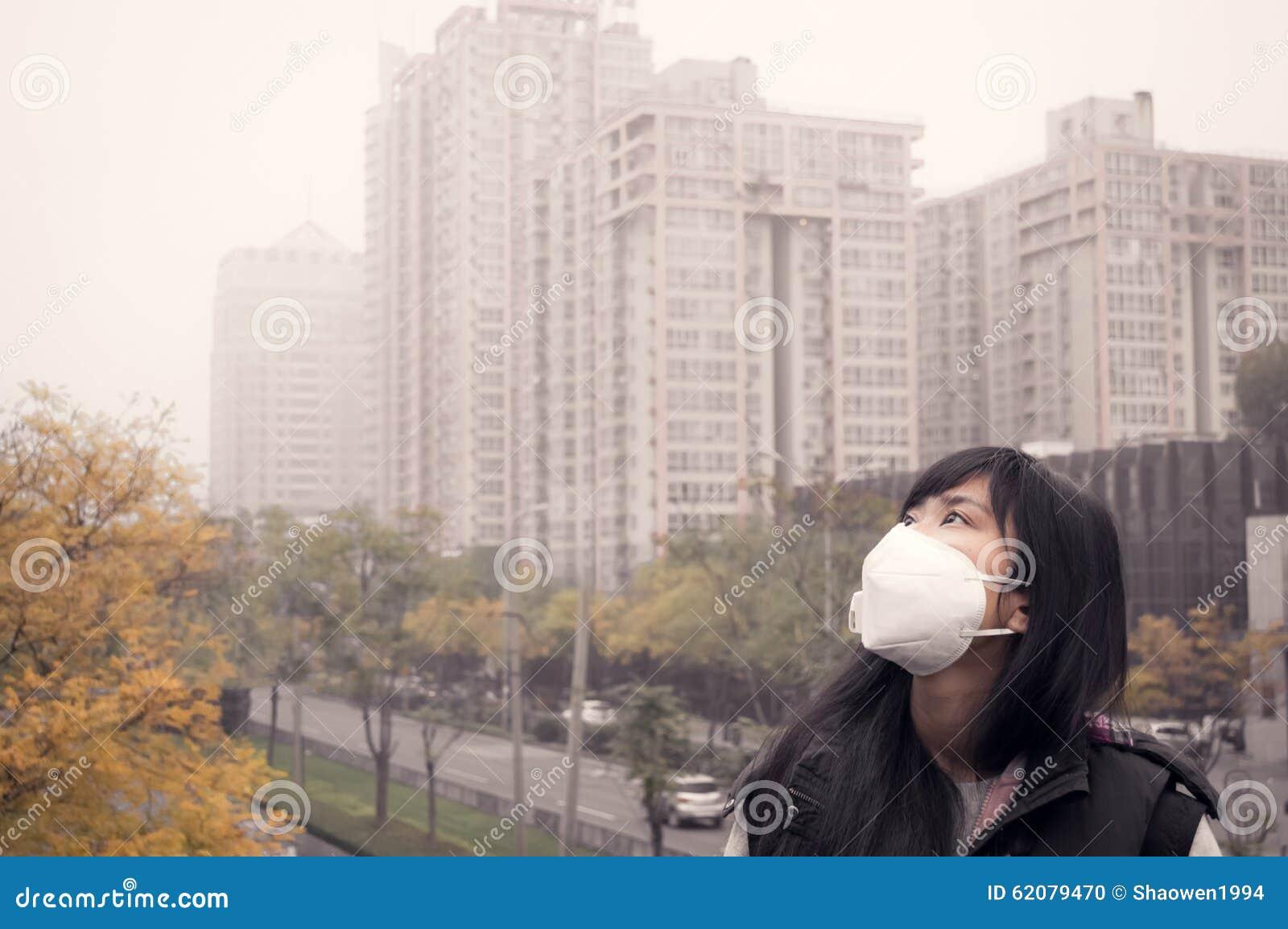 Máscara vestindo da boca da menina asiática contra a poluição do ar do embaçamento