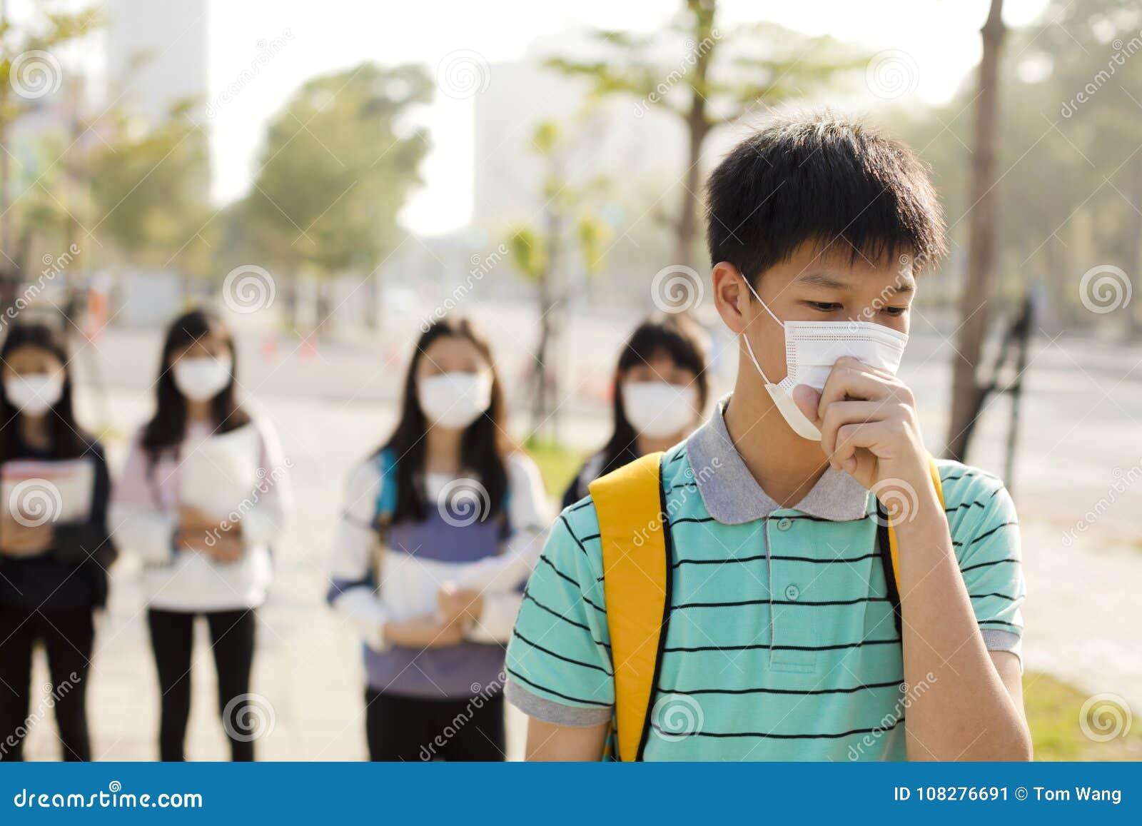 Máscara vestindo da boca do estudante contra a poluição atmosférica na cidade