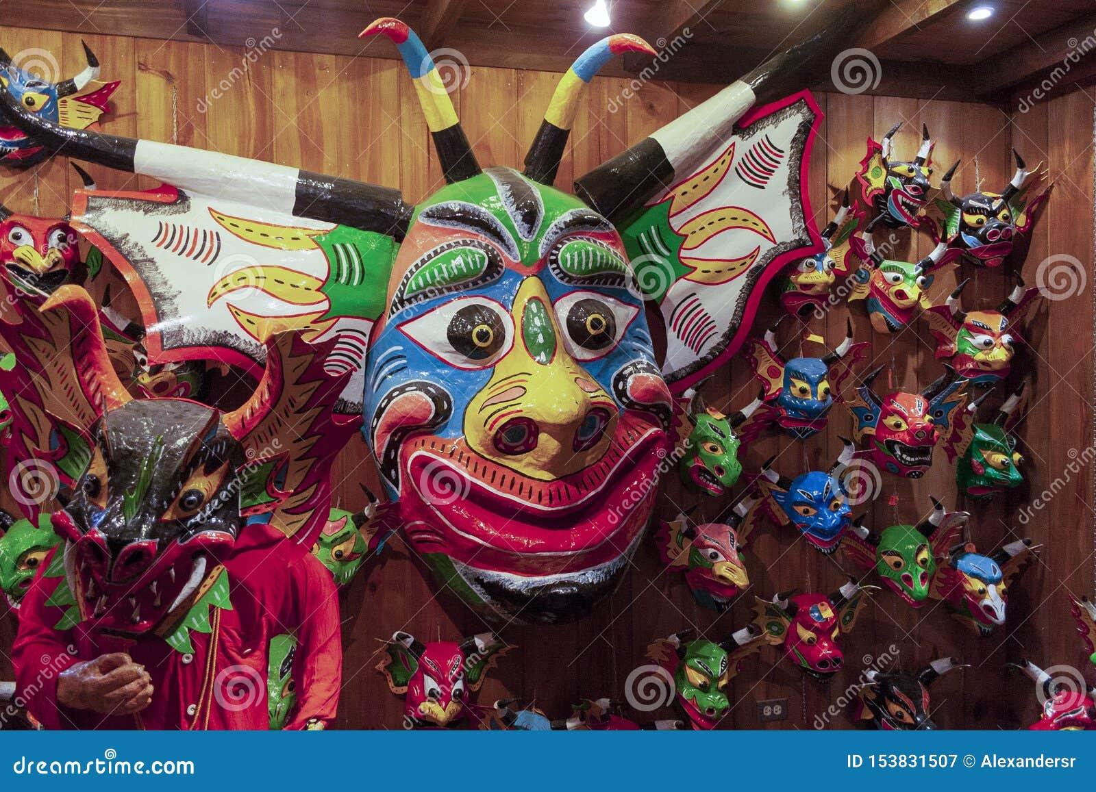 Máscaras icónicas y maniquíes que llevan los trajes de los diablos maniobrables que bailan Corpus Christi en una tienda de souven