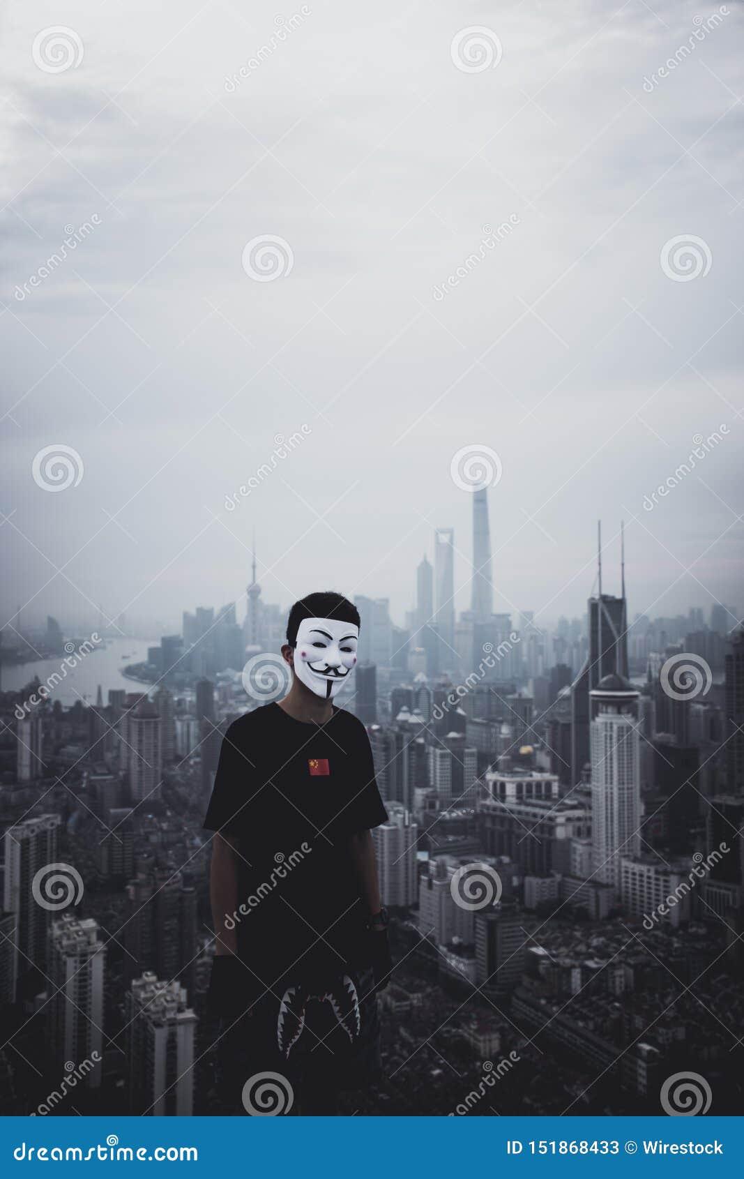 Mâle portant un masque anonyme se tenant sur un toit avec une ville urbaine étonnante dans le dos