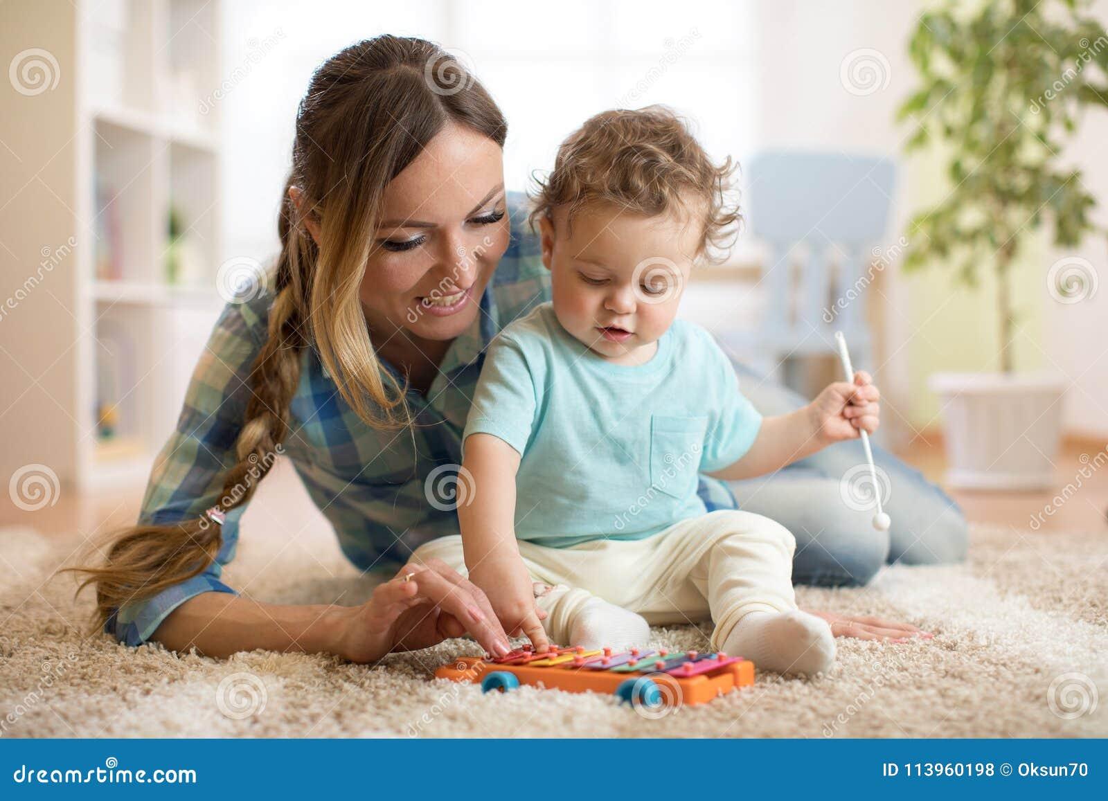 A mãe é ensinando a criança como jogar o brinquedo do xilofone