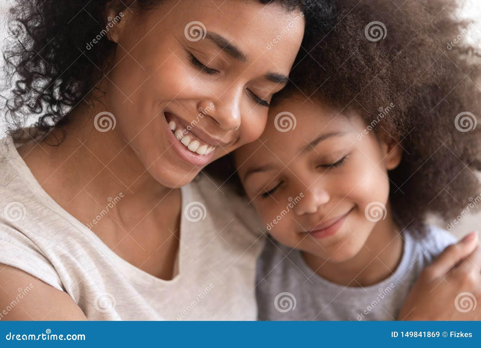 Mãe africana nova de amor que guarda a filha bonito de abraço da criança