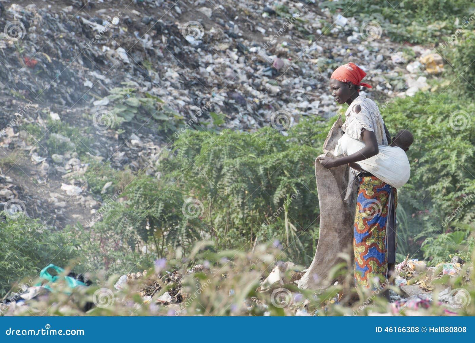 Mãe africana que recolhe recyclables do tr
