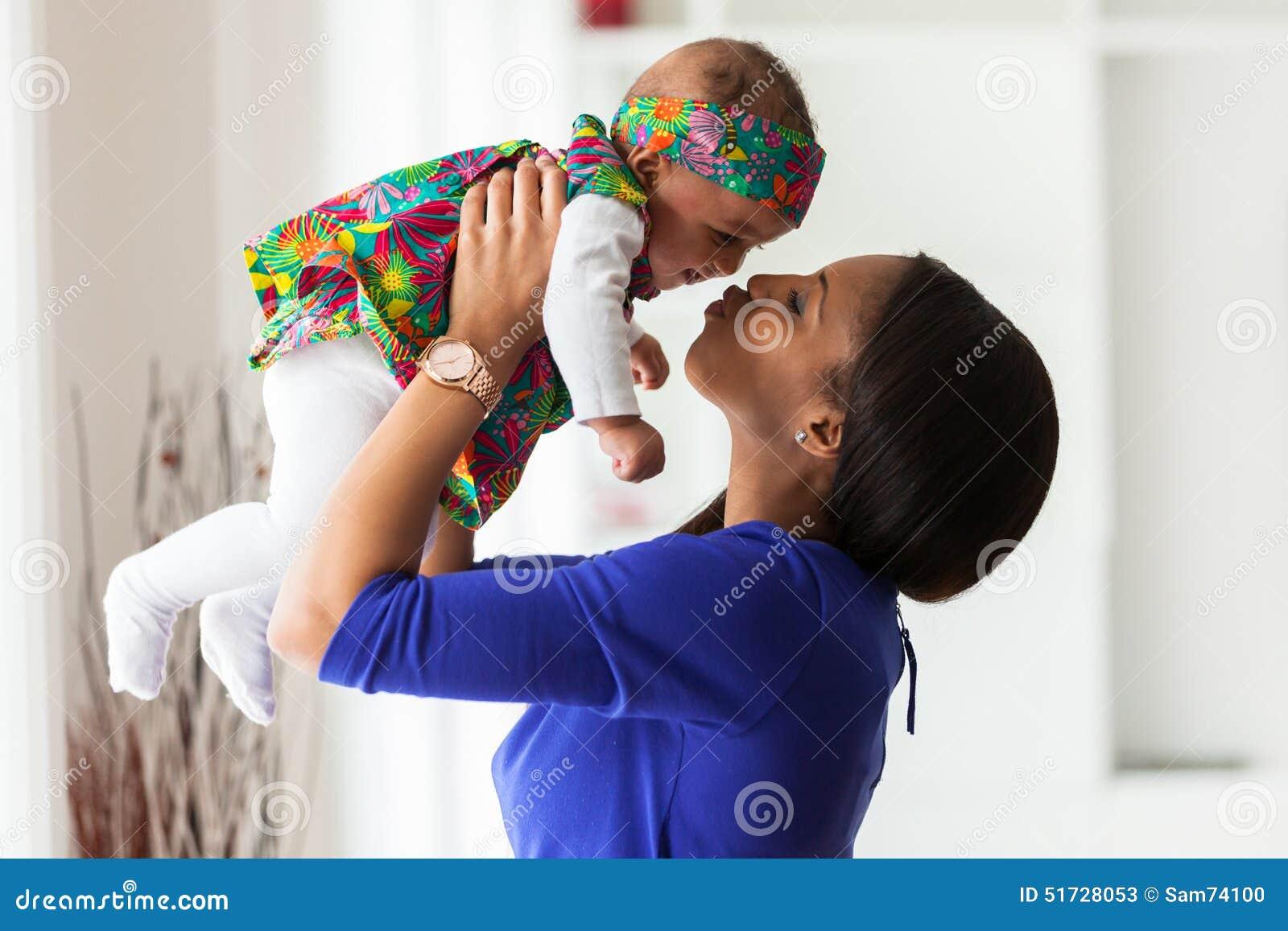 Mãe afro-americano nova que joga com seu bebê