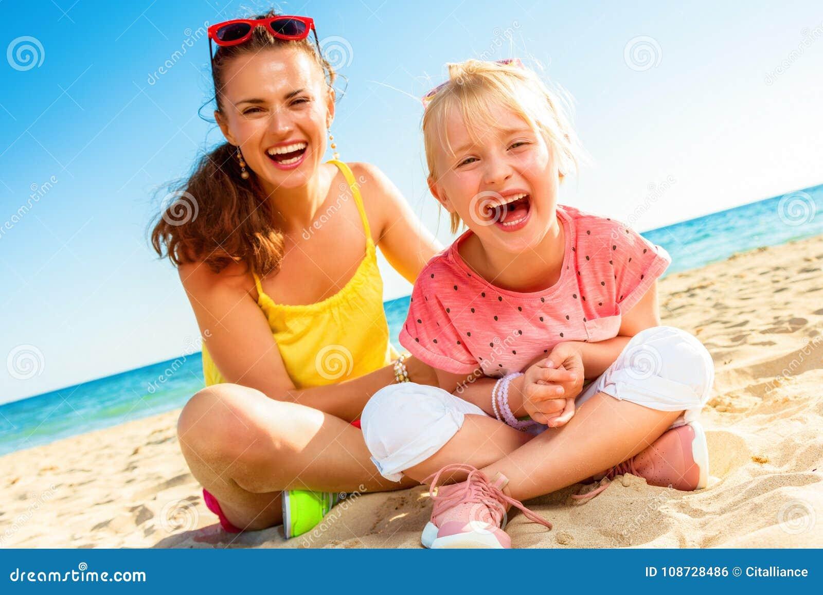 Mãe alegre e criança modernas que sentam-se na praia
