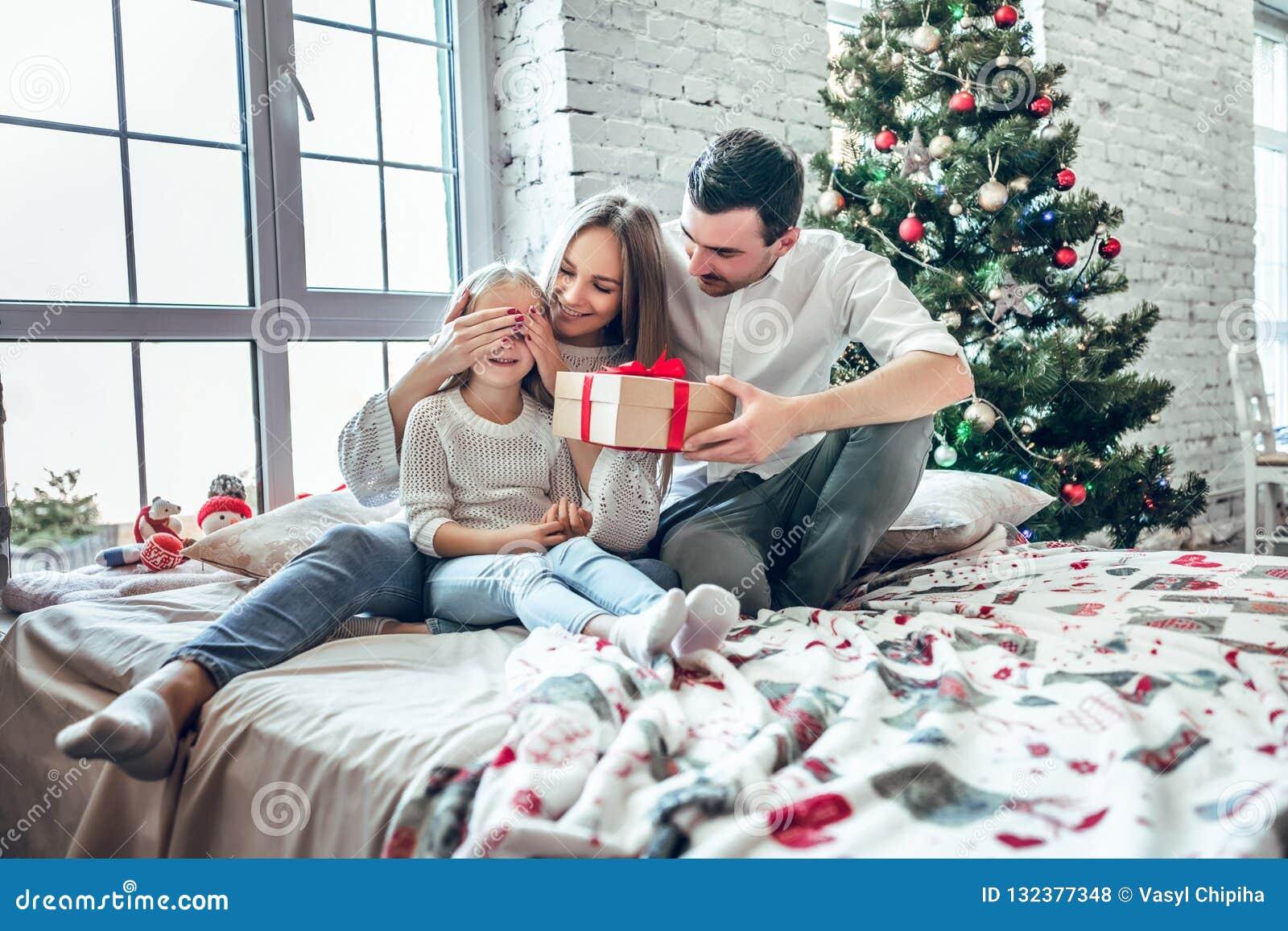 Mãe alegre, pai e sua menina bonito da filha trocando presentes Pai e pouca criança que têm o divertimento perto da árvore de Nat