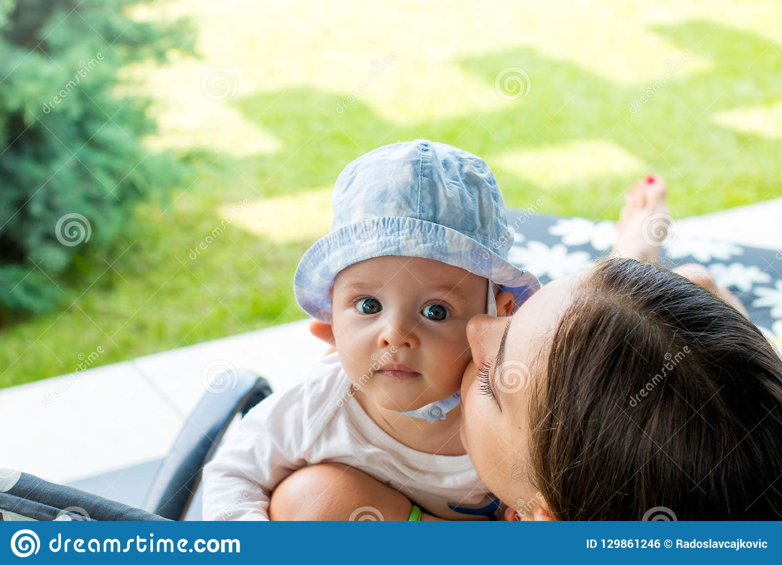 Mãe alegre que abraça, afagando e mordente que beijam o bebê eyed azul bonito