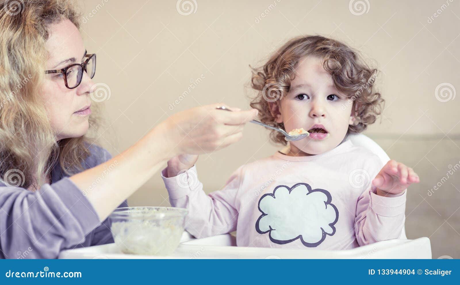 A mãe alimenta seu bebê bonito com uma colher