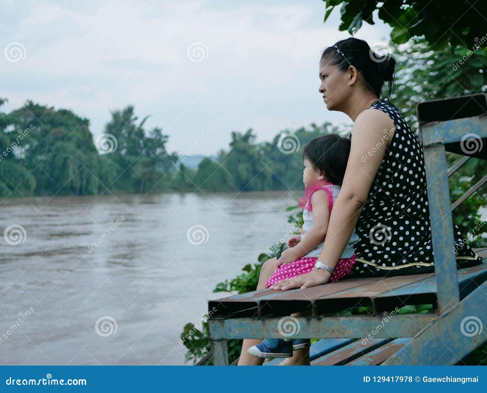 Mãe asiática e sua filha pequena por seu lado que olha o rio enlameado escuro após a precipitação