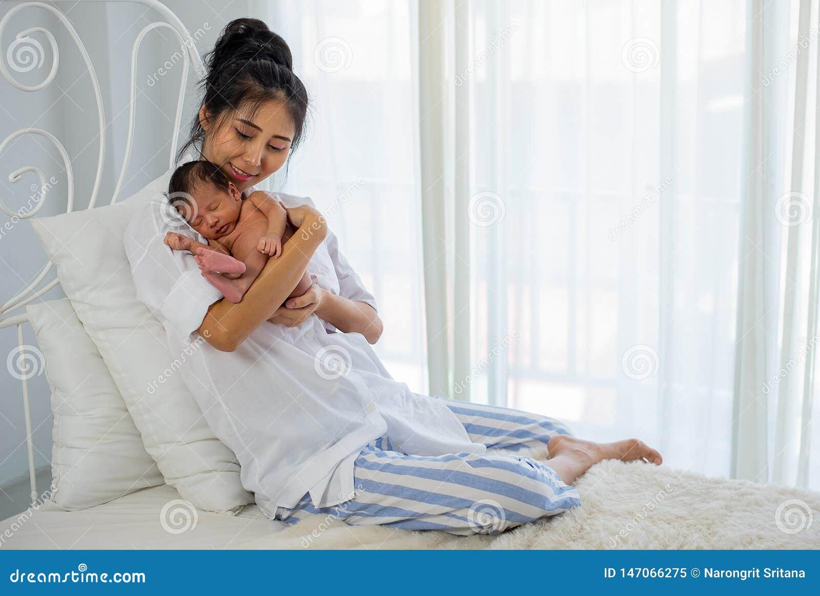 A mãe branca asiática da camisa guarda seu bebê recém-nascido de sono pequeno em sua caixa e senta-se na cama branca na frente da