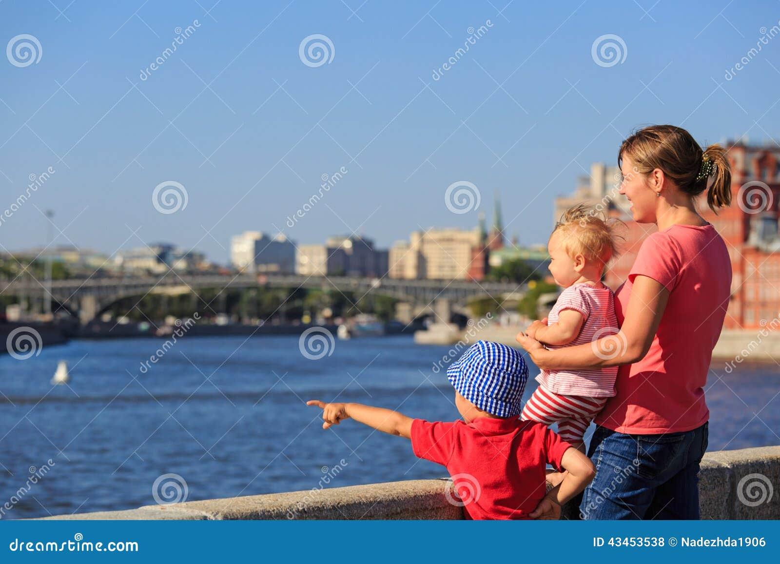 Mãe com as crianças que olham a cidade do verão