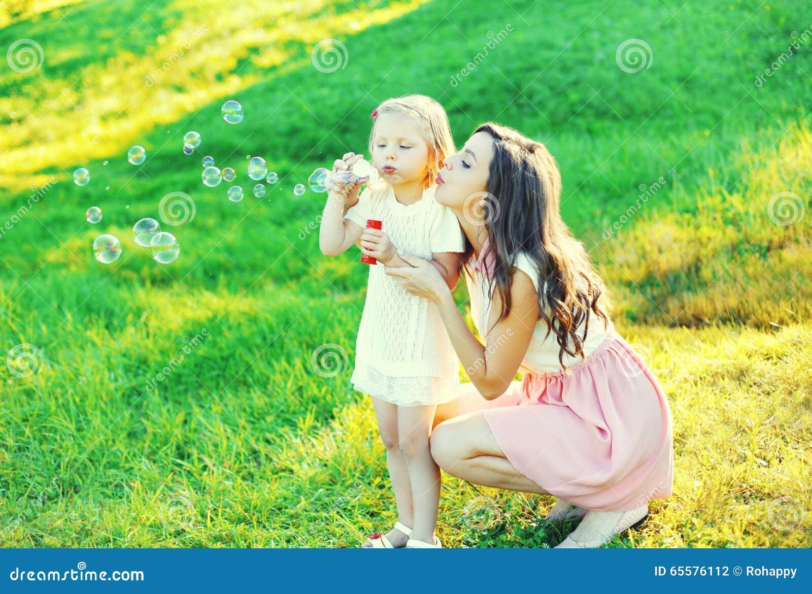 Mãe com bolhas de sabão de sopro da criança junto na grama