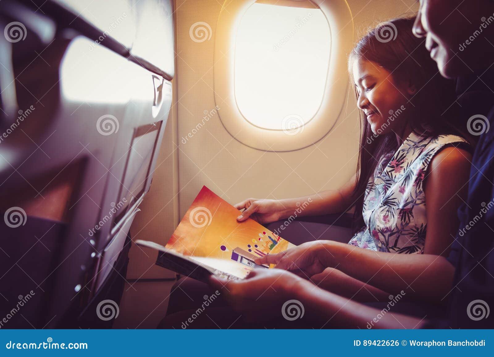 A mãe com filha senta-se em seu lugar no avião