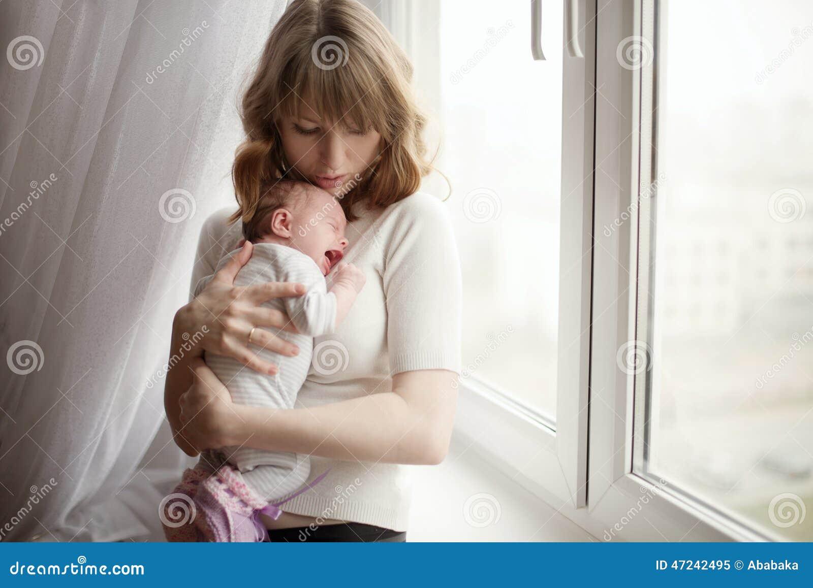 Mãe com o bebê de grito pequeno bonito