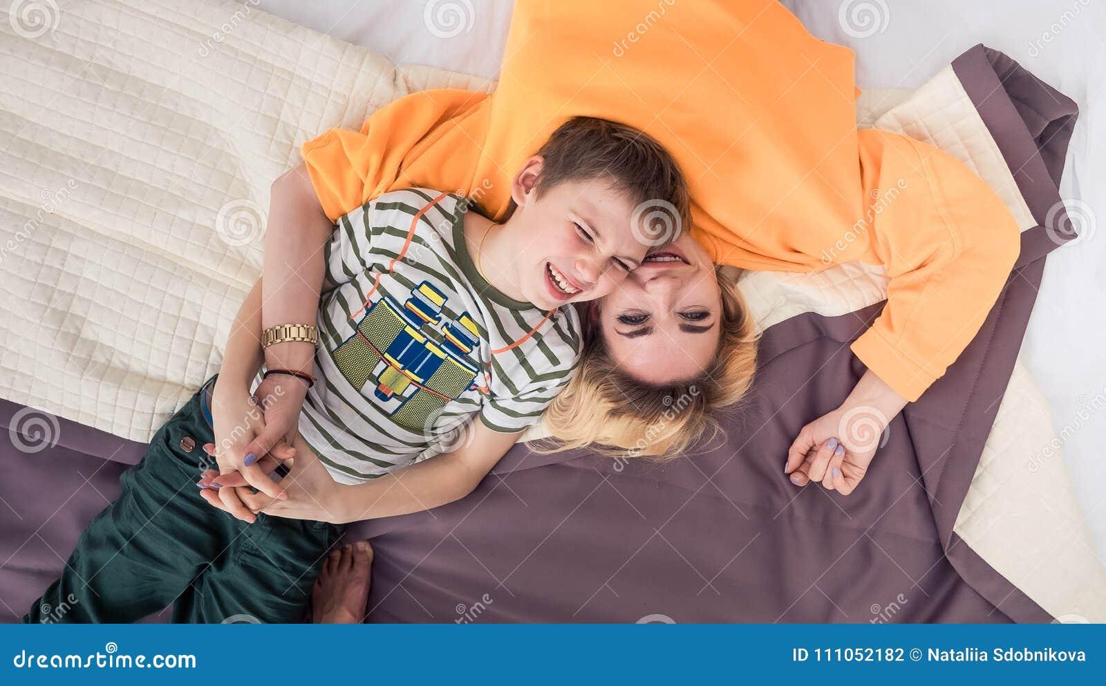 Mãe com o filho na cama, mãe e filho que têm o divertimento