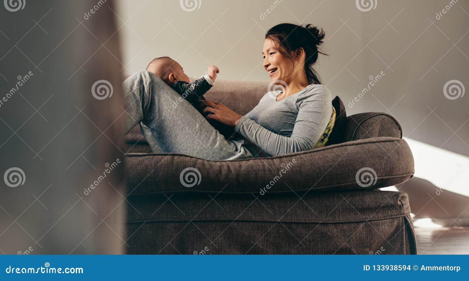 Mãe com seu bebê que senta-se em um sofá