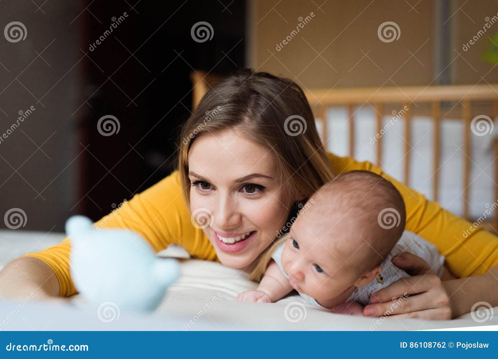 Mãe com seu filho recém-nascido do bebê que encontra-se na cama