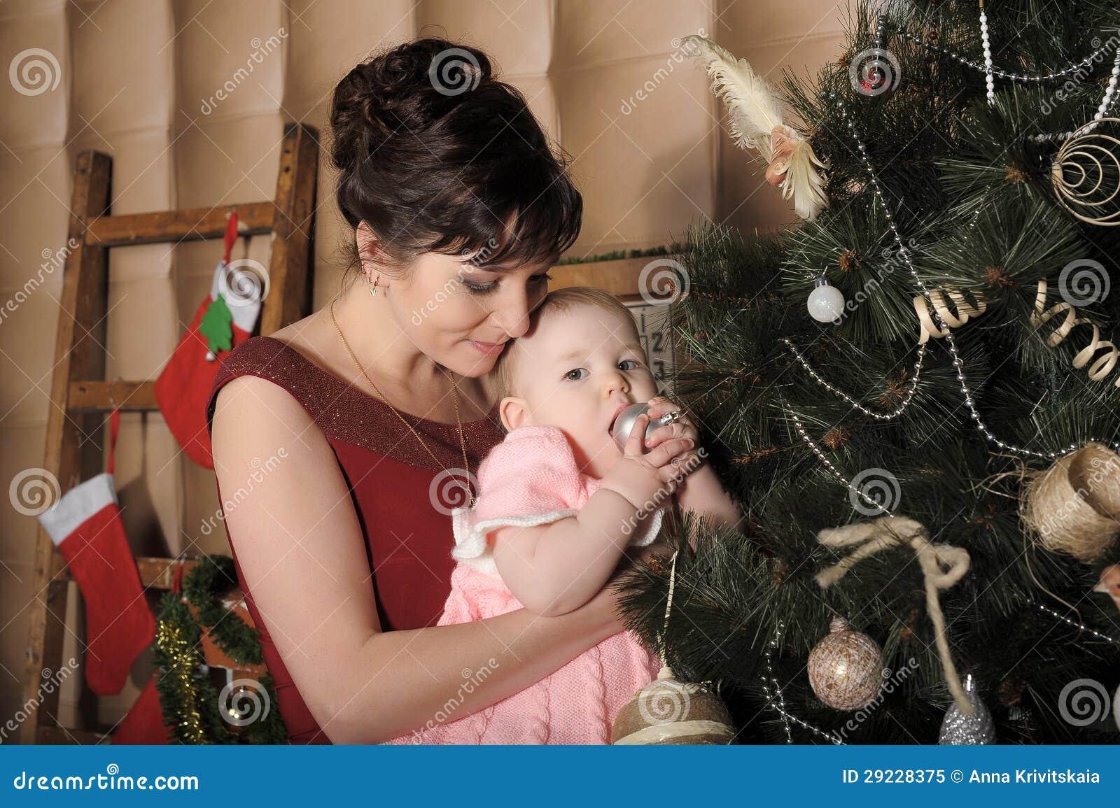 Download Mãe Com Sua Filha Em Seus Braços Perto Da árvore De Natal Imagem de Stock - Imagem de dezembro, christmas: 29228375