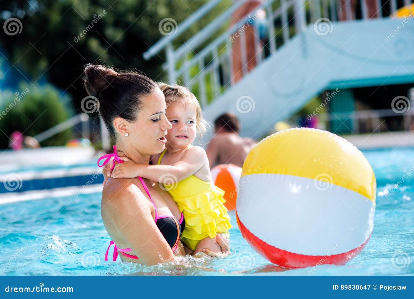 Mãe com sua filha na piscina Verão ensolarado