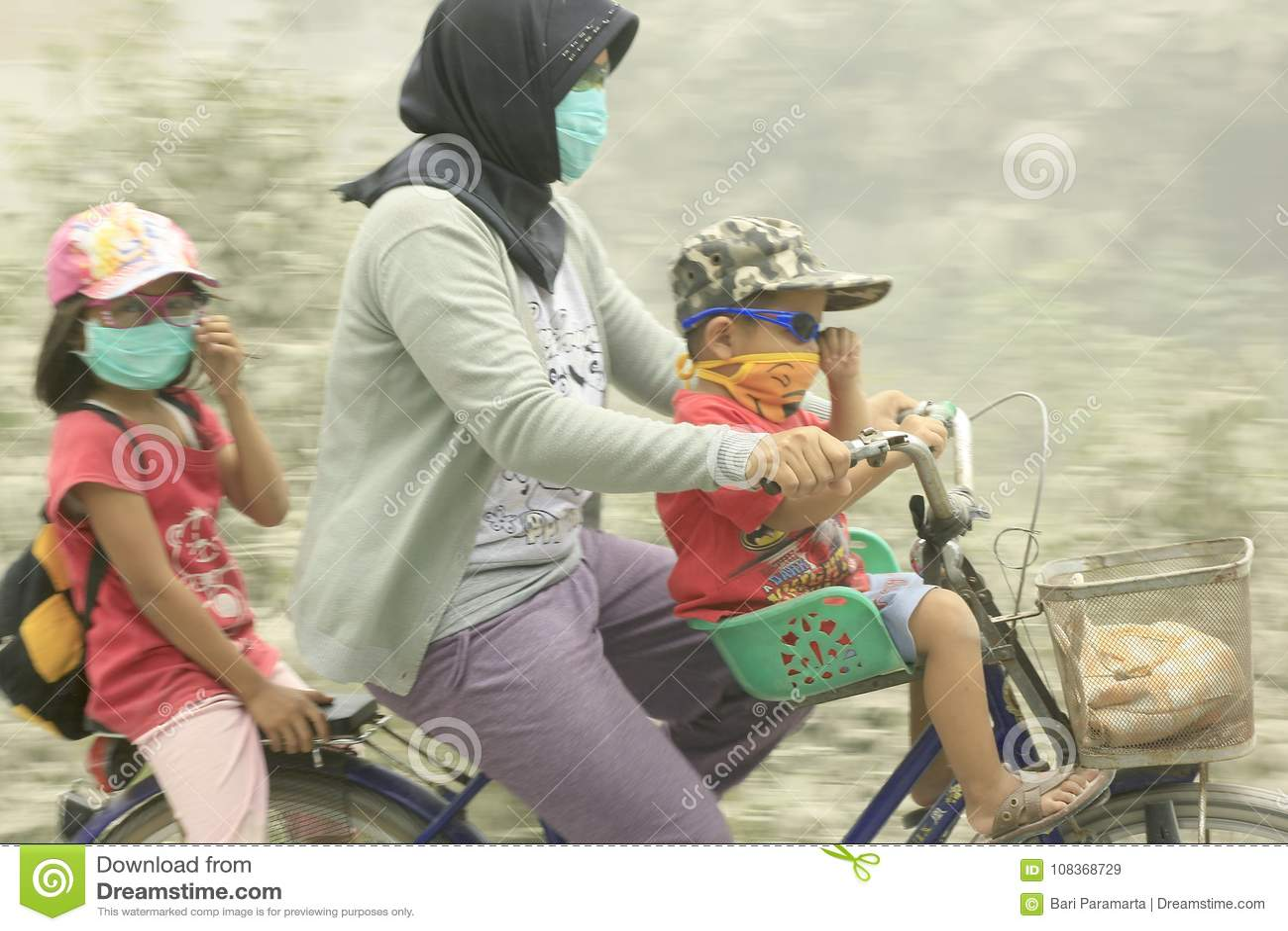 Mãe com suas duas crianças através de uma montagem Kelud da erupção da cinza vulcânica