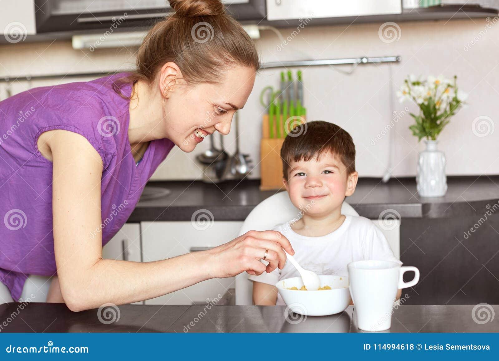 A mãe contente alimenta sua criança masculina pequena com colher, dá o papa de aveia delicioso e o chá, promete ir para a caminha