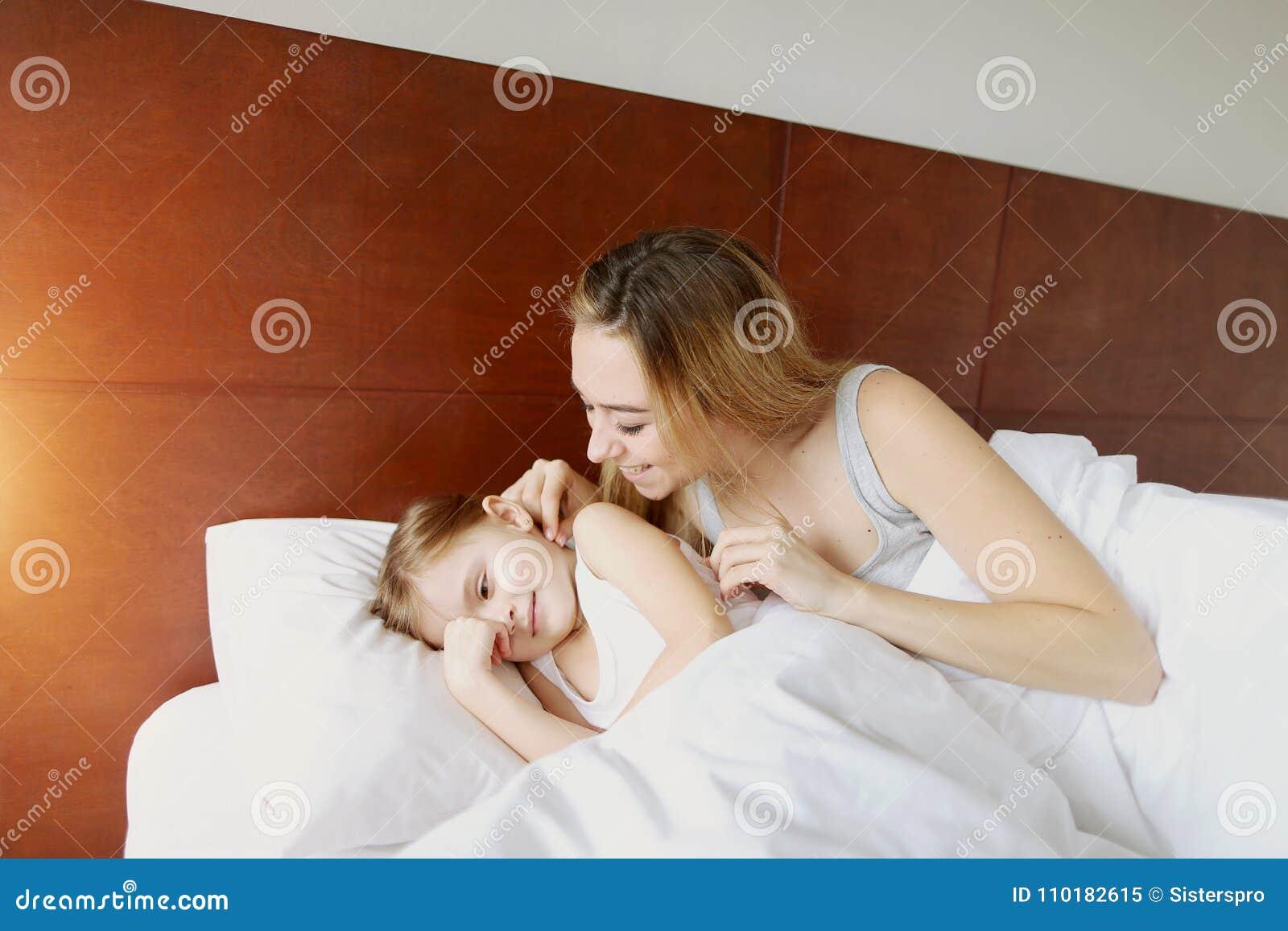 A mãe da beleza acorda a filha pequena na cama branca com luz do sol