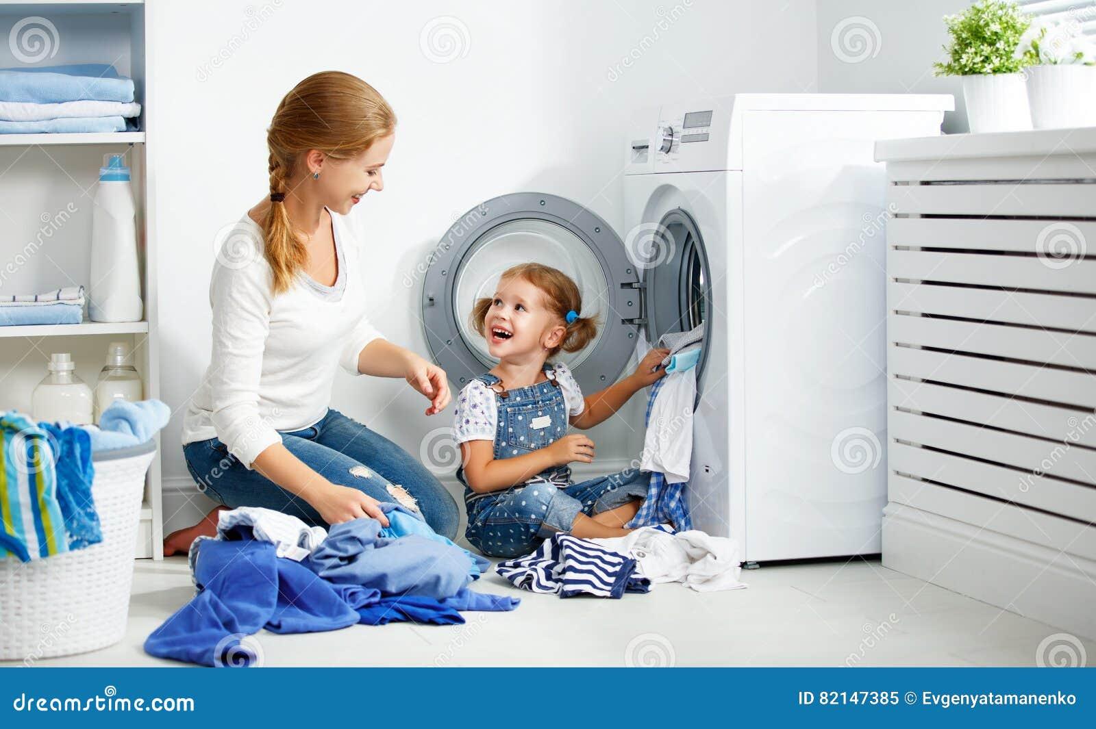 Mãe da família e ajudante pequeno da criança na lavandaria perto do washi