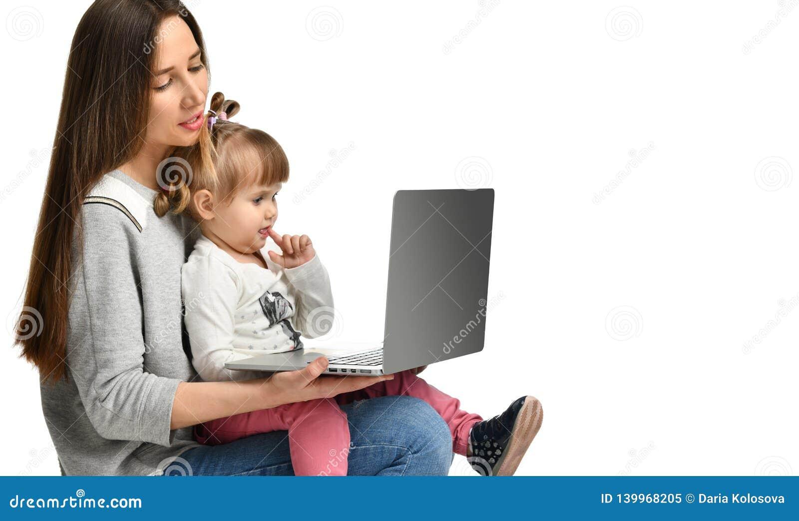 Mãe da família e filha da criança em casa com um portátil