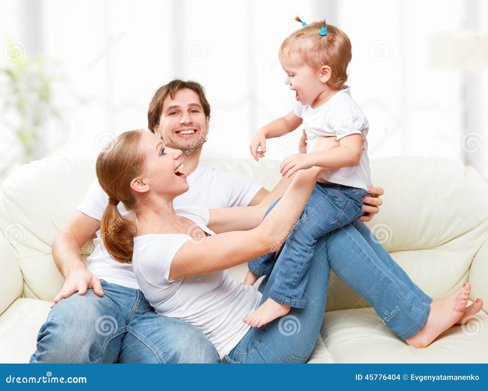 Mãe da família, pai, filha do bebê da criança em casa no sofá que joga e riso felizes