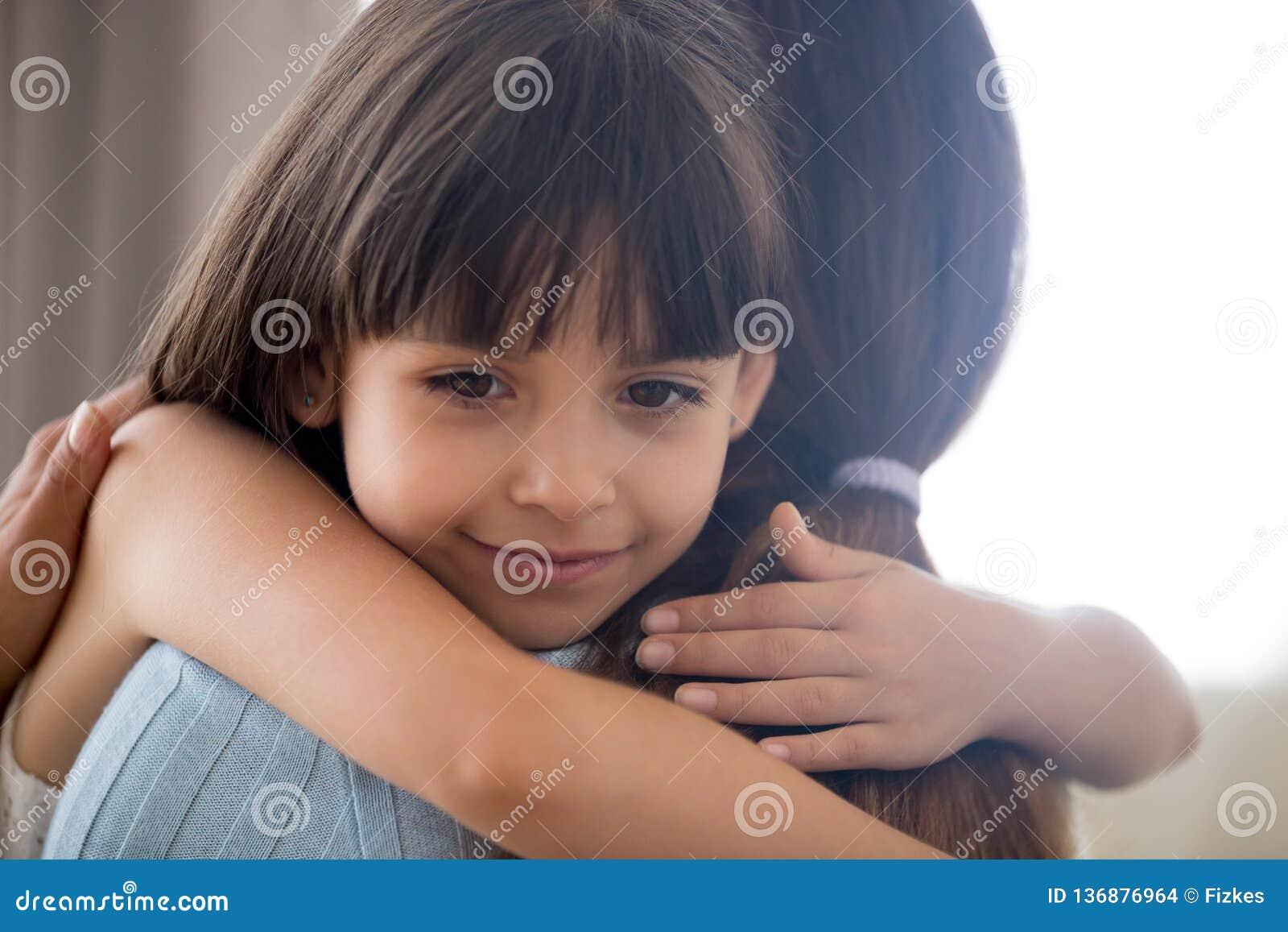 Mãe de amor de abraço da menina bonito da criança pequena que guarda a comida ruminada apertada