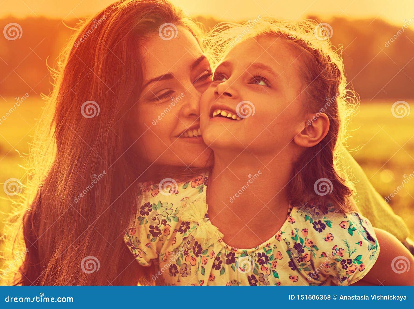 Mãe de apreciação feliz que abraça sua menina de riso brincalhão da criança na luz ensolarada do por do sol no fundo do verão clo