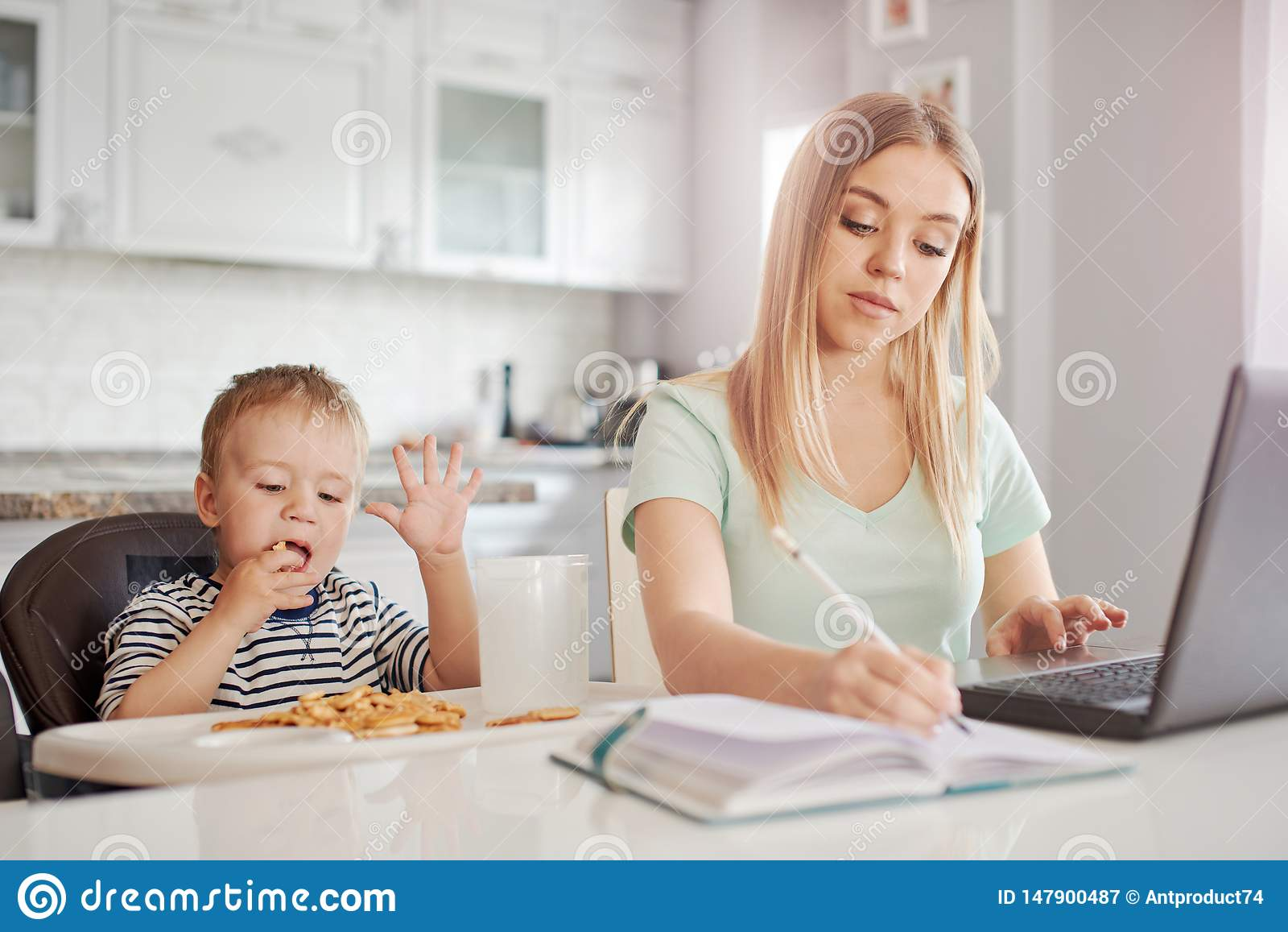 Mãe de funcionamento com a criança na cozinha