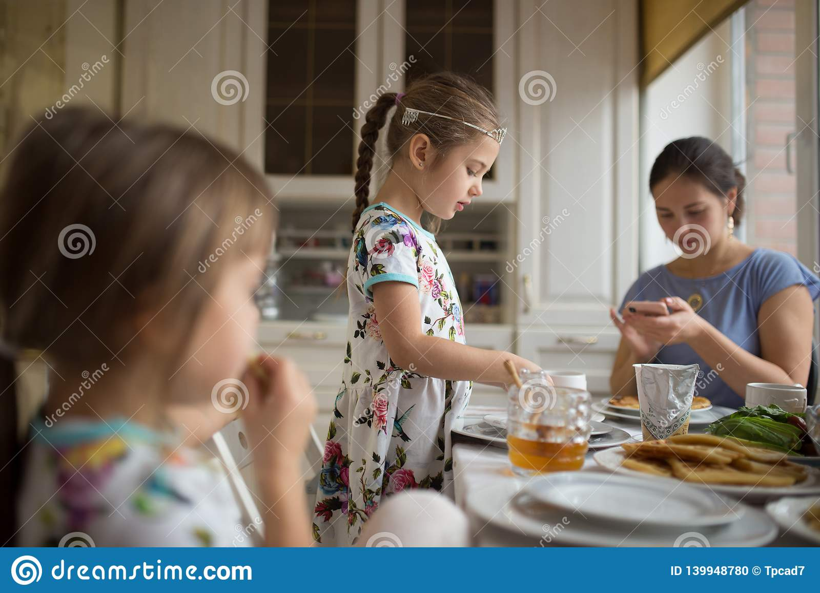 Mãe de inquietação nova e suas duas filhas pequenas que comem panquecas com mel no café da manhã na cozinha acolhedor