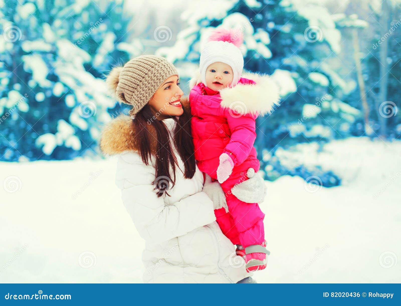 Mãe de sorriso feliz do retrato do inverno com o bebê em suas mãos sobre a árvore de Natal nevado
