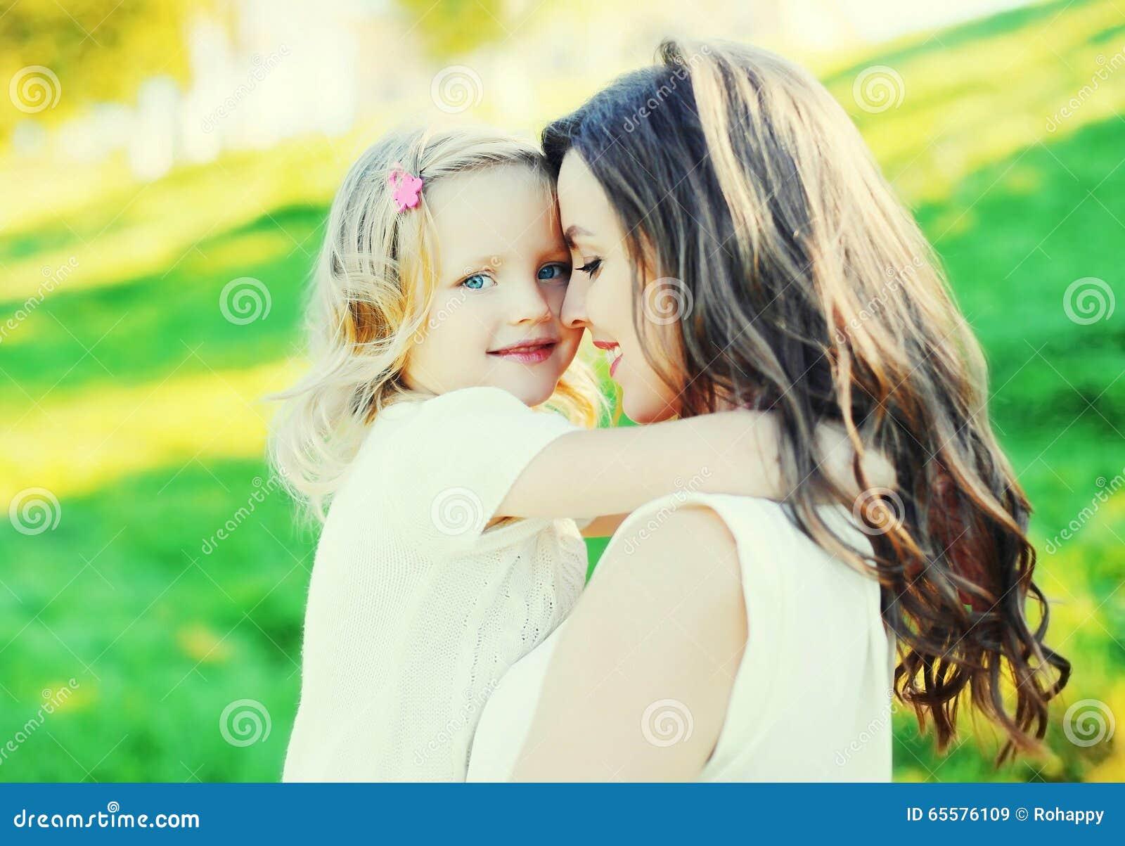 Mãe de sorriso feliz do retrato que abraça a filha da criança