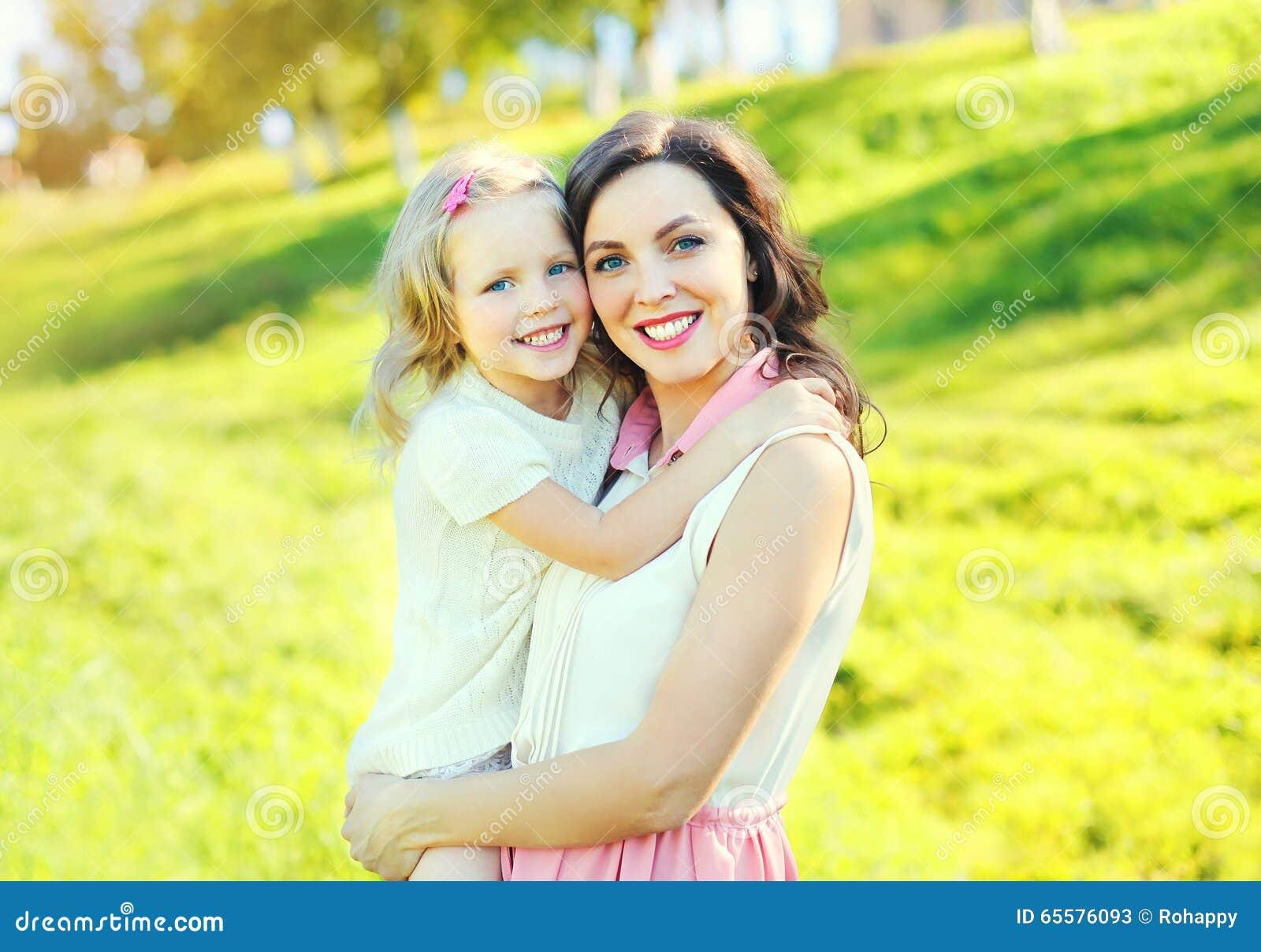 Mãe de sorriso feliz que abraça a filha da criança no verão