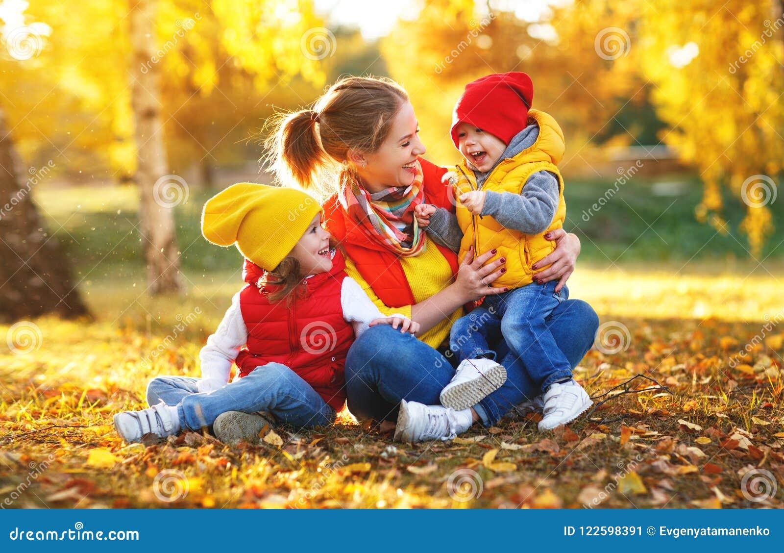 A mãe e as crianças felizes da família no outono andam