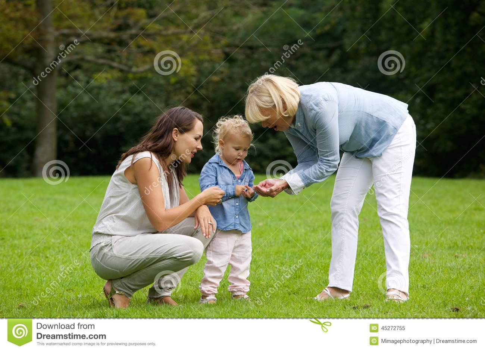 Mãe e avó que mostram a flor da menina