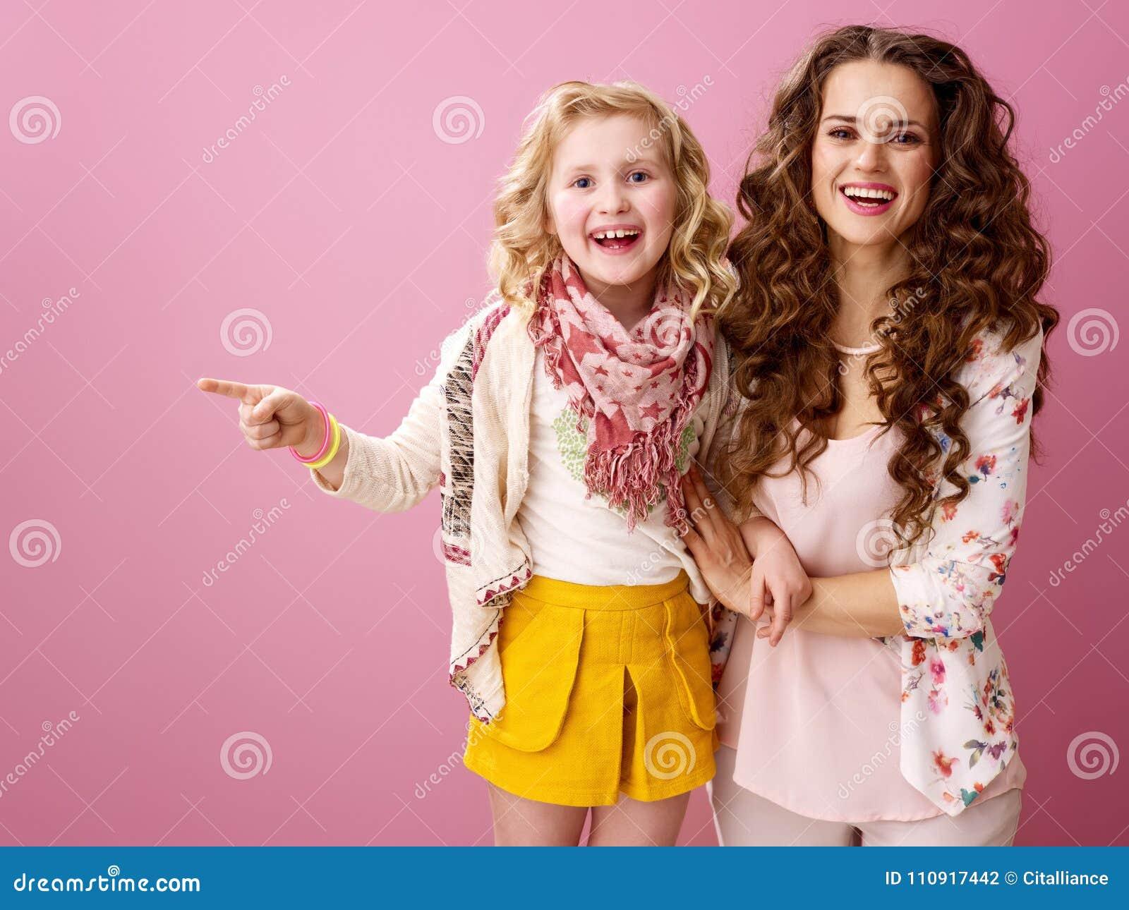 Mãe e criança de sorriso isoladas em apontar cor-de-rosa em algo