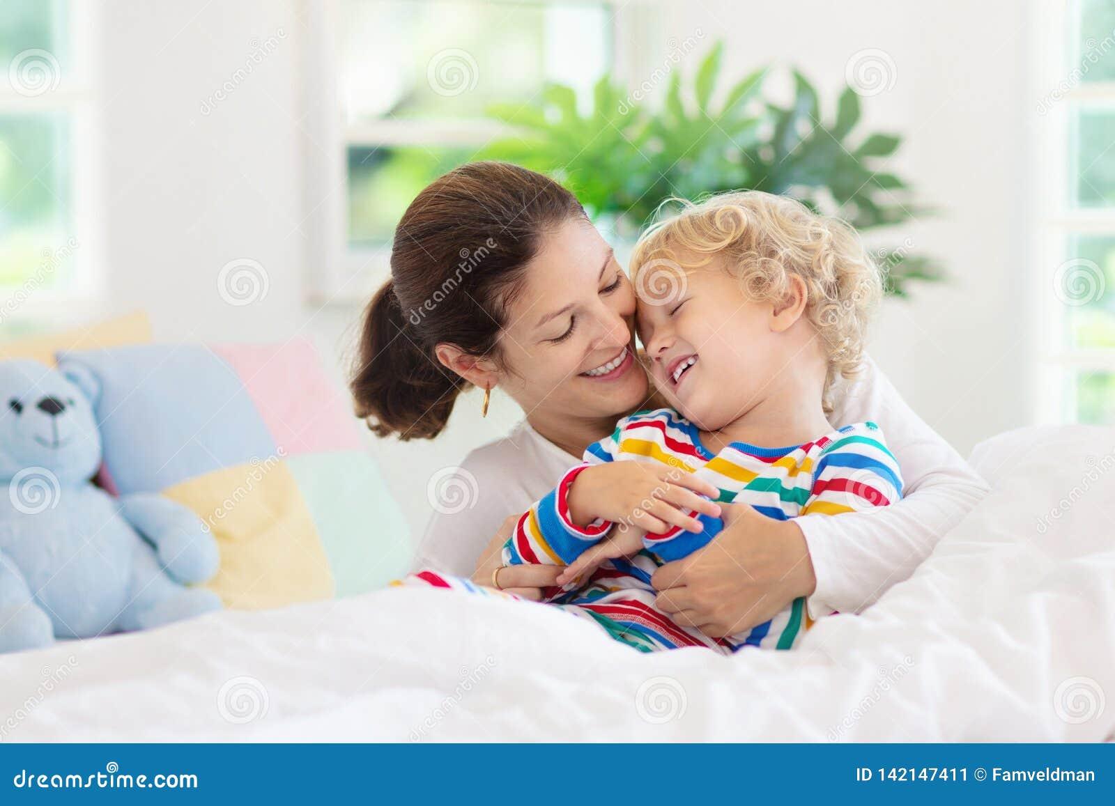 Mãe e criança na cama Mamã e bebê em casa