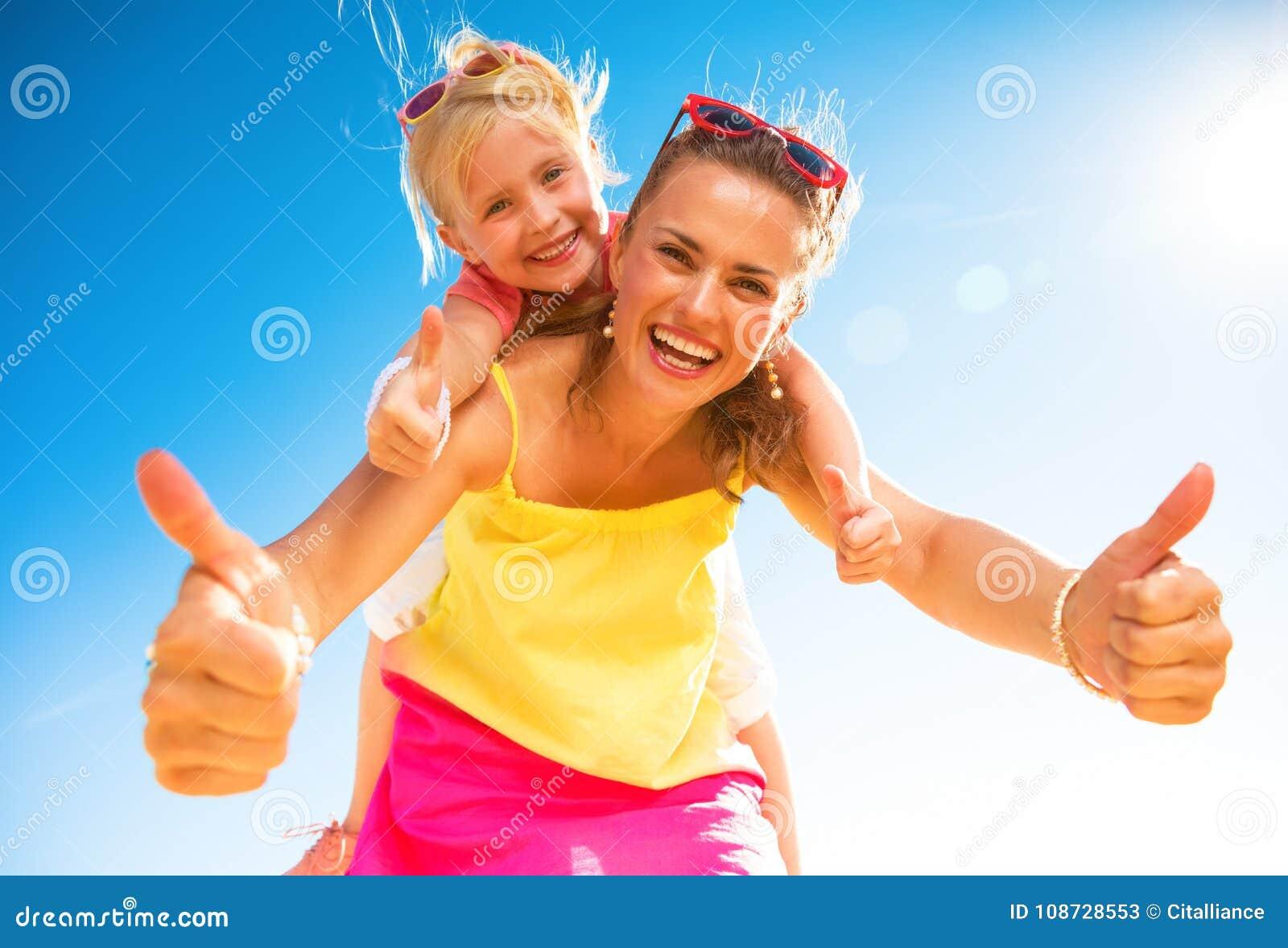 Mãe e criança na moda de sorriso na praia que mostra os polegares acima