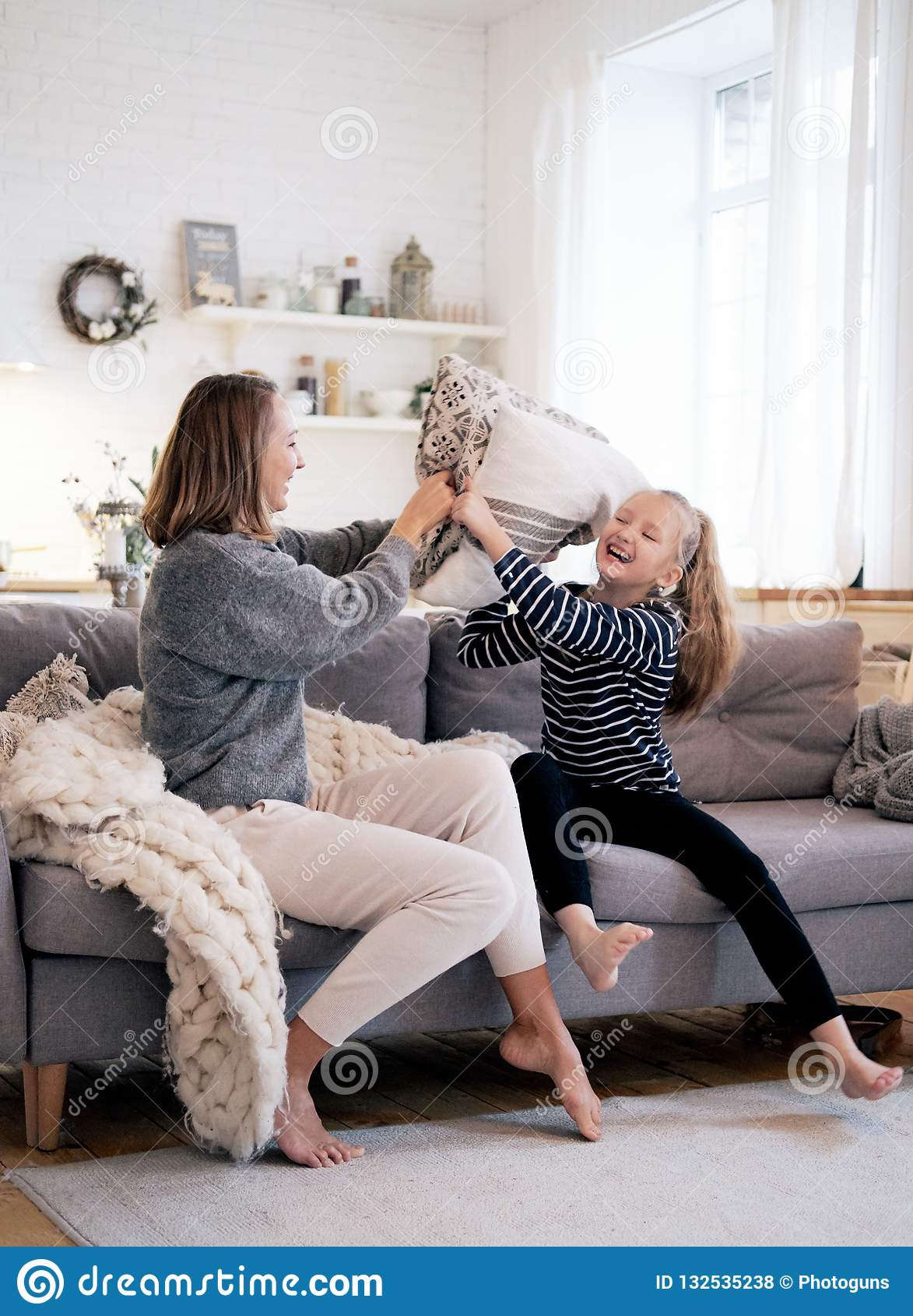 Mãe e criança que têm o divertimento na luta de descanso no sofá-cama no quarto Família feliz que passa o tempo junto