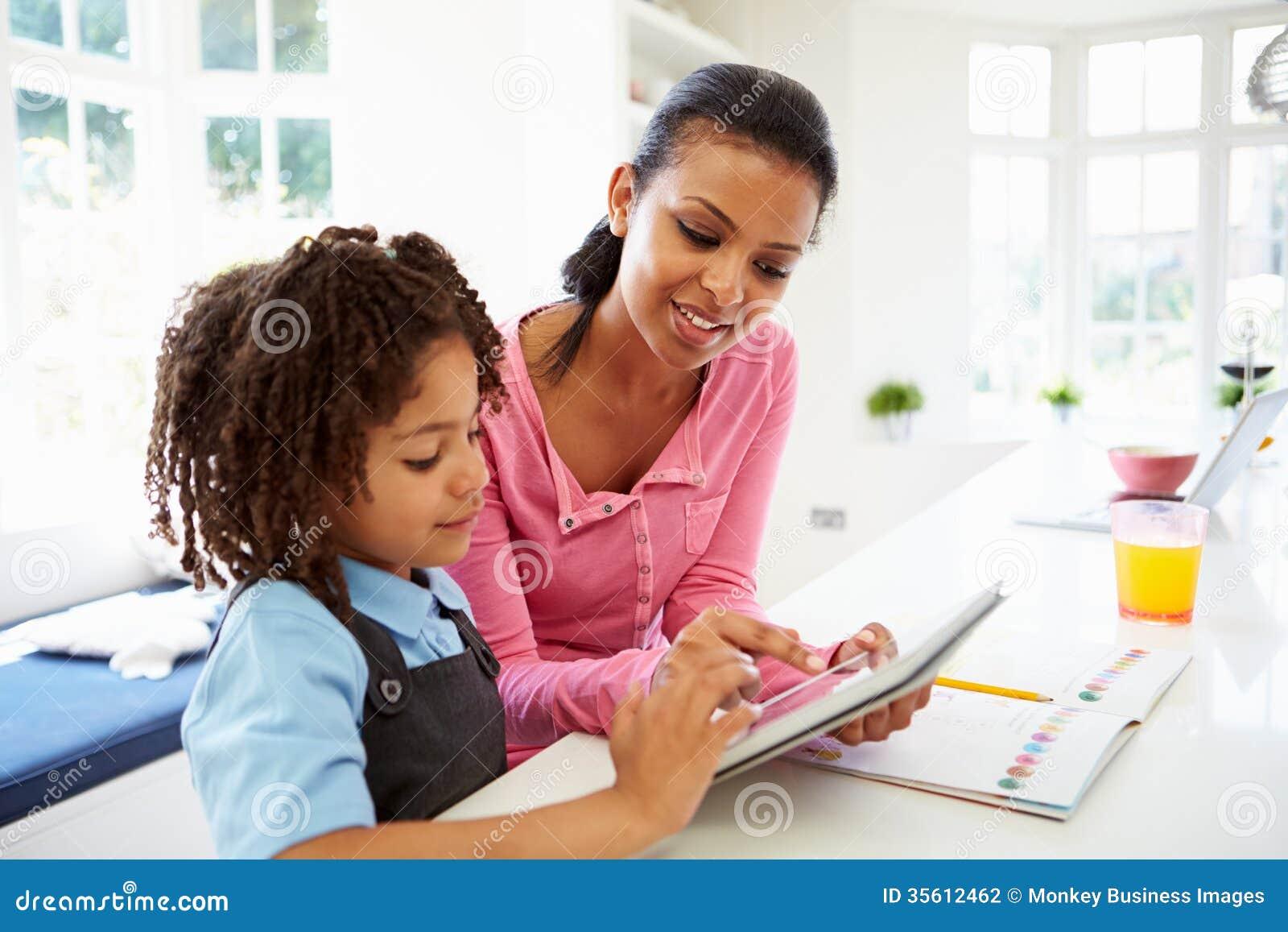 Mãe e criança que usa a tabuleta de Digitas para trabalhos de casa