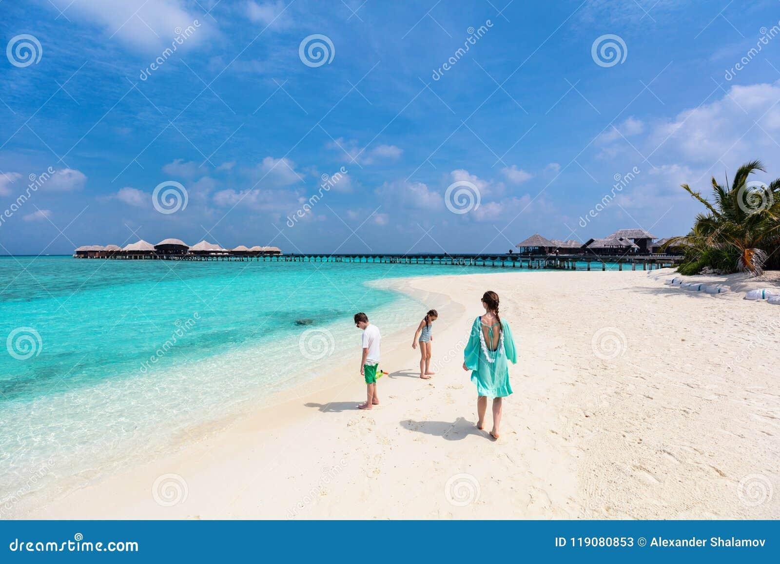 Mãe e crianças na praia tropical